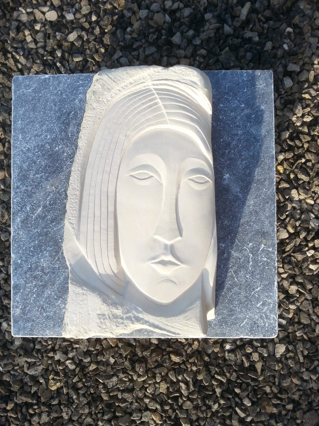 Carved stone stylised face in Caen limestone
